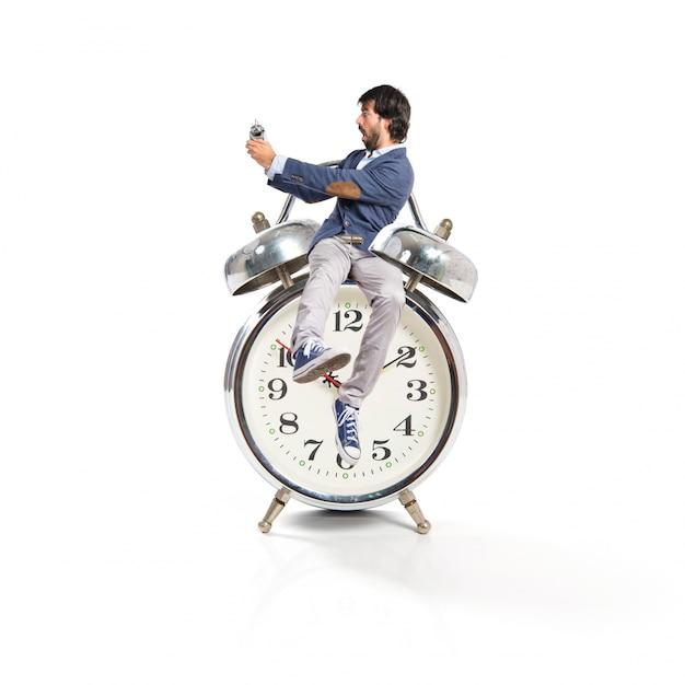 Hombre que sostiene un reloj sobre fondo blanco