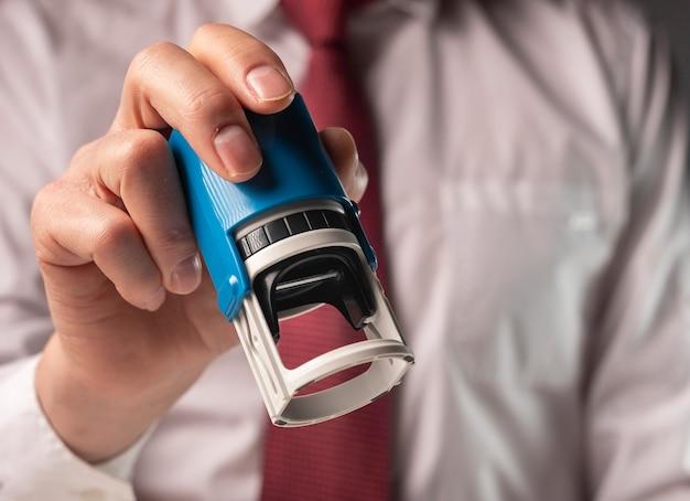 Hombre que sostiene el sello de goma de cerca. el empresario certifica documentos.