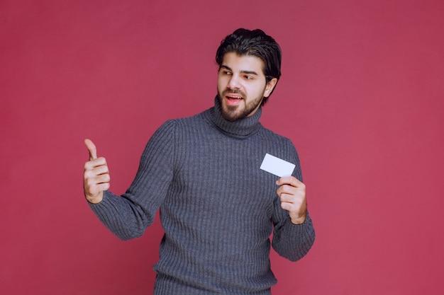Hombre que sostiene su tarjeta de visita y hace un signo de mano positivo.