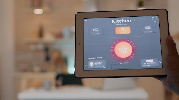 Hombre que sostiene la tableta con la aplicación de control de iluminación, encendiendo las luces sentado en la cocina con sistema de iluminación de automatización