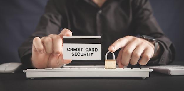 Hombre que sostiene la tarjeta de crédito y el candado. seguridad de la tarjeta de crédito