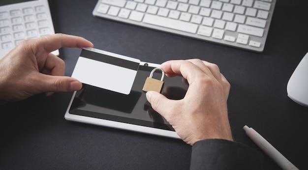 Hombre que sostiene la tarjeta de crédito y el candado seguridad de la tarjeta de crédito