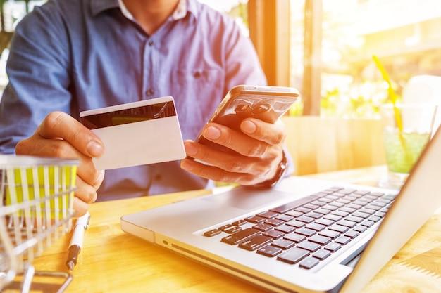 Hombre que sostiene la tarjeta de crédito en la mano y que incorpora el código de seguridad usando el teclado del ordenador portátil