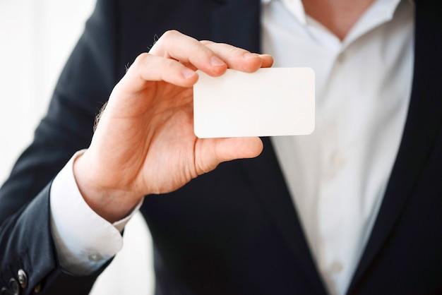 Hombre que sostiene la tarjeta plástica en blanco