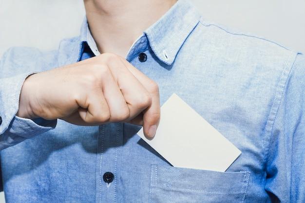 Hombre que sostiene la tarjeta de presentación blanca sobre fondo de muro de hormigón, plantilla de maqueta.