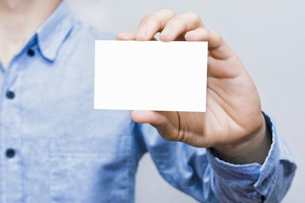 Hombre que sostiene la tarjeta de visita blanca sobre fondo de pared de hormigón, plantilla de maqueta