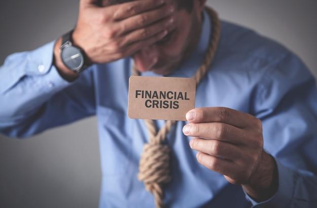 Hombre que sostiene la tarjeta de visita marrón. crisis financiera