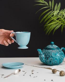 Hombre que sostiene la taza de té azul
