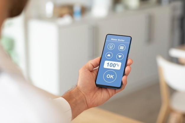 Hombre que sostiene un teléfono inteligente con una aplicación de automatización del hogar