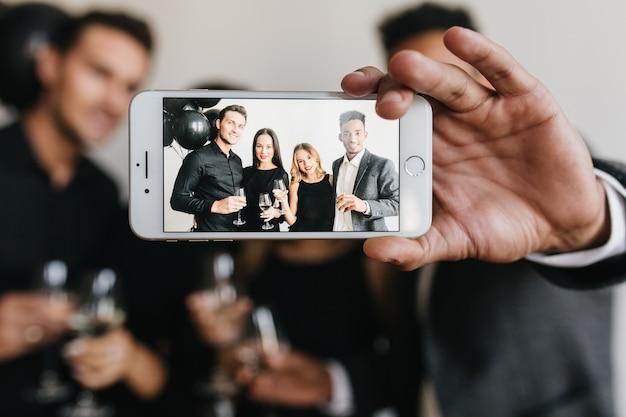 Hombre que sostiene el teléfono inteligente blanco con la imagen de los jóvenes con gafas en la pantalla