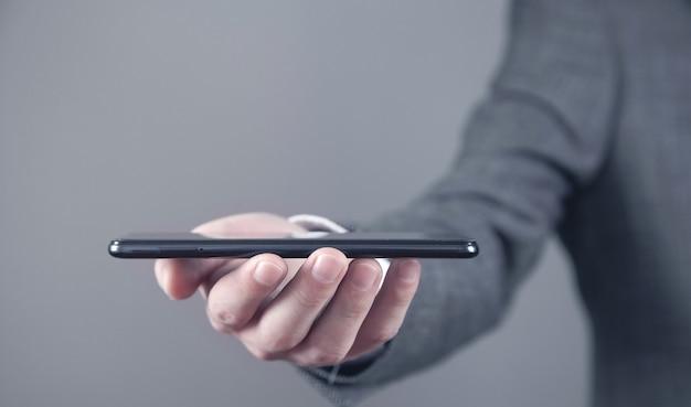 Hombre que sostiene el teléfono inteligente. concepto de tecnología