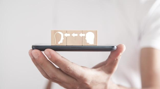 Hombre que sostiene el teléfono inteligente con cubos de madera. cabezas humanas. transferencia de conocimiento