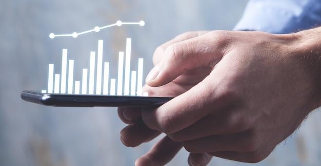 Hombre que sostiene el teléfono inteligente con un gráfico de negocios. concepto de negocio
