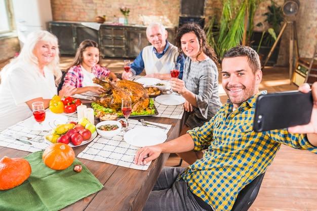 Hombre que sostiene teléfono inteligente en la mesa con la familia