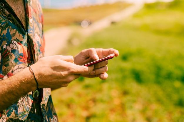 Hombre que sostiene teléfono inteligente en la naturaleza