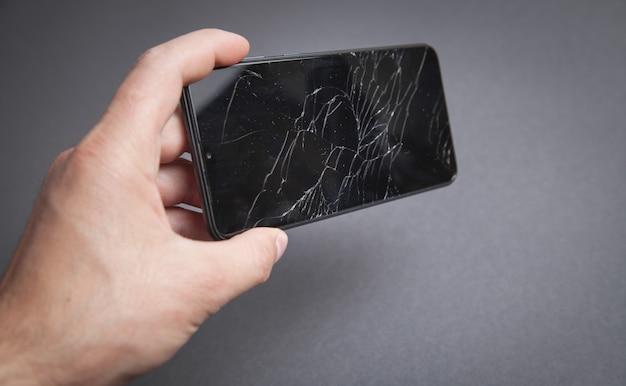 Hombre que sostiene el teléfono inteligente negro roto. pantalla rota