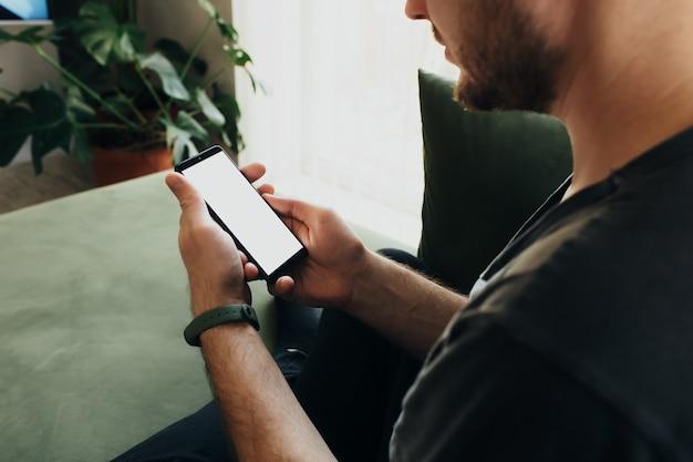 Hombre que sostiene el teléfono inteligente con pantalla blanca