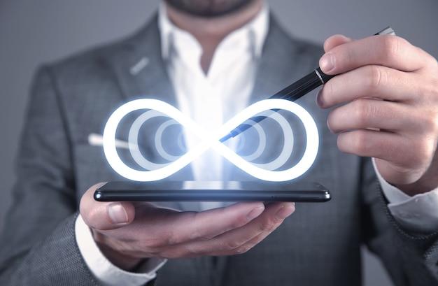 Hombre que sostiene el teléfono inteligente con un símbolo de infinito.