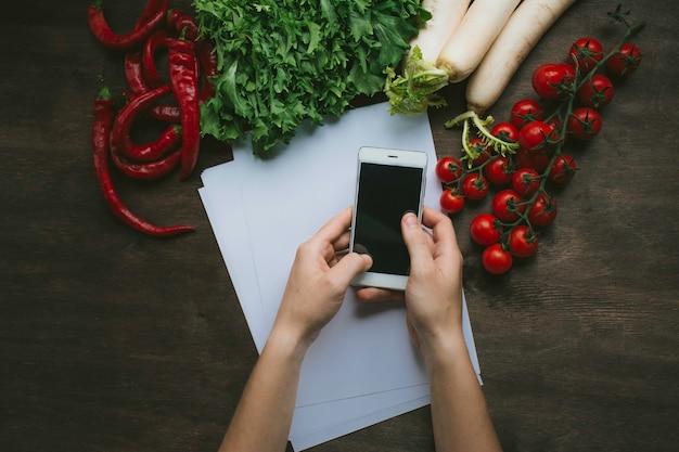 Un hombre que sostiene un teléfono inteligente en sus manos sobre la mesa de la cocina sobre un fondo con verduras frescas. lay flat
