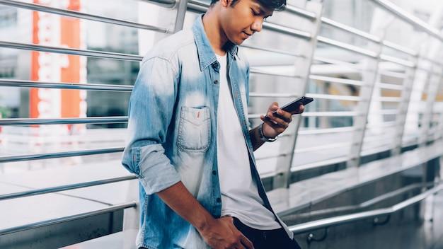 Hombre que sostiene un teléfono inteligente. usando el teléfono celular en el estilo de vida. tecnología para el concepto de comunicación.