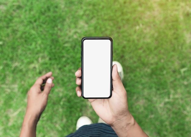 Hombre que sostiene el teléfono que muestra la pantalla en blanco caminando sobre el césped