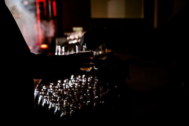 Hombre que sostiene un vaso de bebida mientras que un camarero lo ayuda, contraluz con fondo negro.