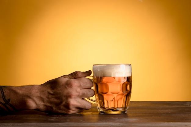 Hombre que sostiene el vaso de cerveza en la mesa de madera