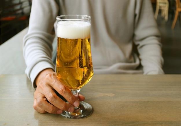 Hombre que sostiene un vaso de cerveza en la mesa de madera