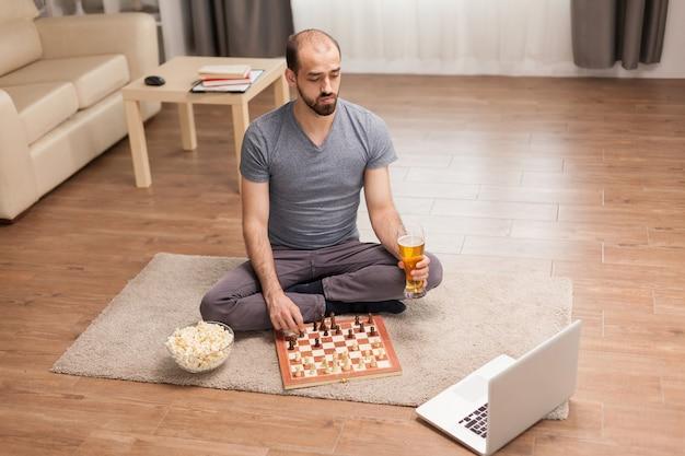 Hombre que sostiene el vaso de cerveza mientras juega al ajedrez en línea durante el autoaislamiento.