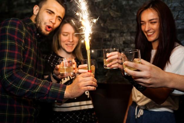 Hombre que sostiene la vela de chispa disfrutando de bebidas con amigos