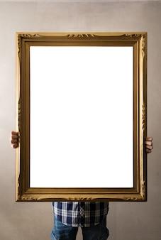 Hombre que sostiene un viejo marco en blanco dorado