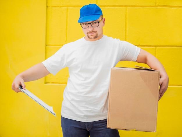 Hombre que sostiene la vista frontal de caja y portapapeles