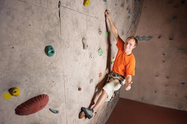 Hombre que sube en la pared práctica en el gimnasio, bouldering. colgando de una mano y levantando el pulgar.