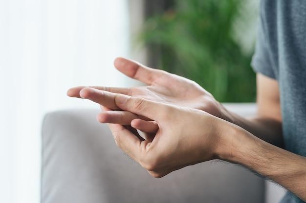 Hombre que sufre de dolor en las articulaciones de las manos y los dedos causas de la artritis reumatoide