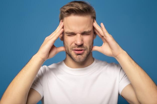 Hombre que sufre de dolor de cabeza con los ojos cerrados aislados en azul