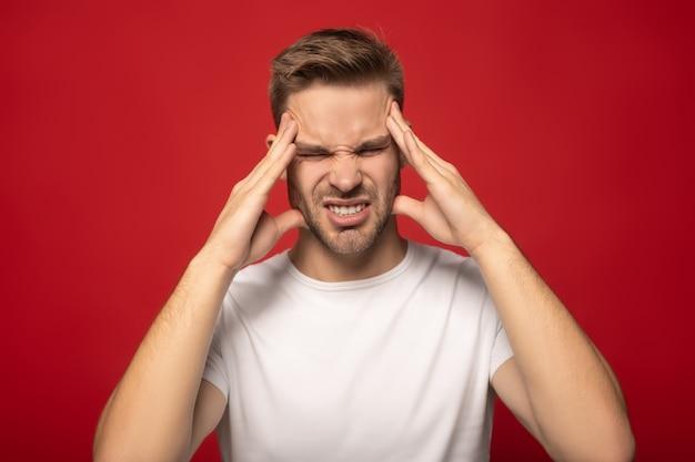 Hombre que sufre de dolor de cabeza con los ojos cerrados aislados en rojo