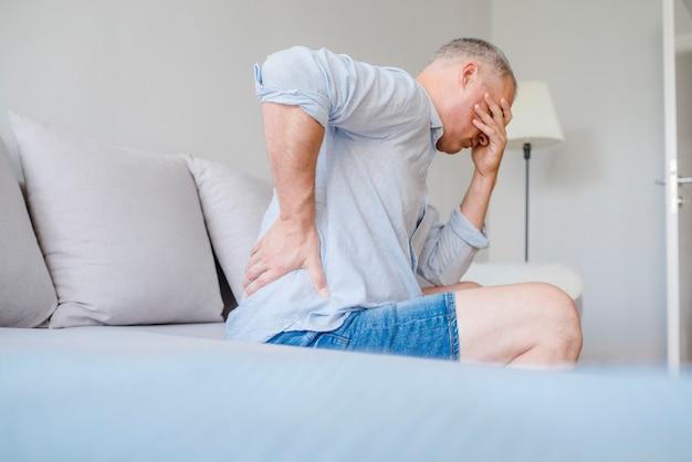 Hombre que sufre de dolor de espalda en casa