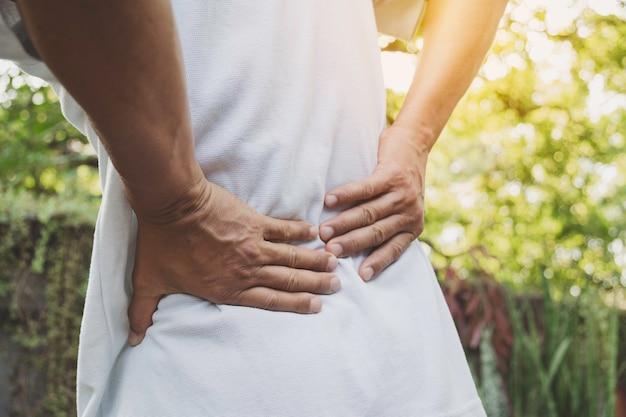 Un hombre que sufre de dolor de espalda, lesión en la columna vertebral y problemas musculares en el exterior.