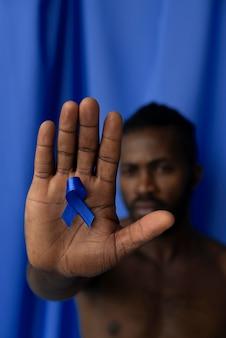 Hombre que tiene una cinta azul en la mano