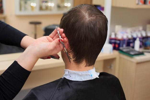 Hombre que tiene un corte de pelo de peluquería. foto de primer plano de afeitarse la cabeza de un hombre