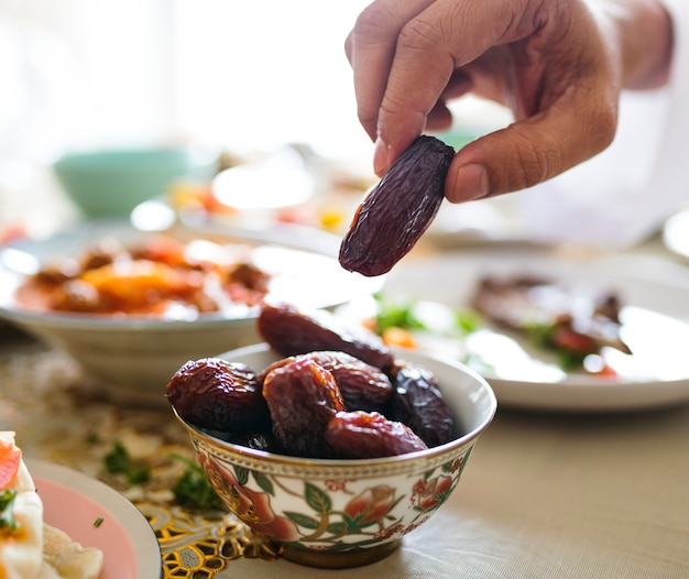 Hombre que tiene una fecha seca en el banquete de ramadán