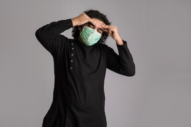 Hombre que tiene fiebre con una máscara médica sentirse enfermo y enfermo.