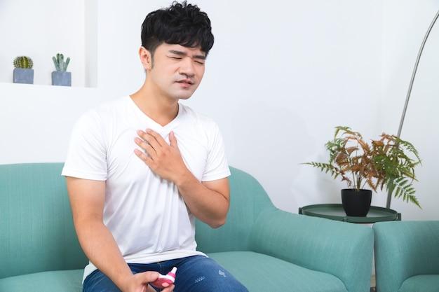 Hombre que tiene opresión en el pecho, dolor en el pecho sentado en el sofá en casa.
