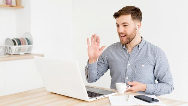 Hombre que tiene video conferencia en la computadora portátil