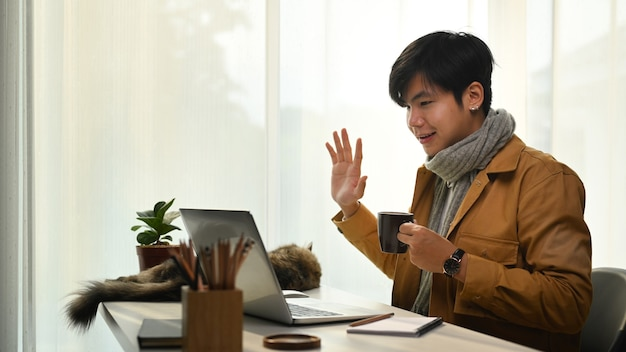 Hombre que tiene videollamada en la computadora portátil y saluda a sus colegas.