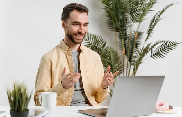 Hombre que tiene videollamada en la computadora portátil