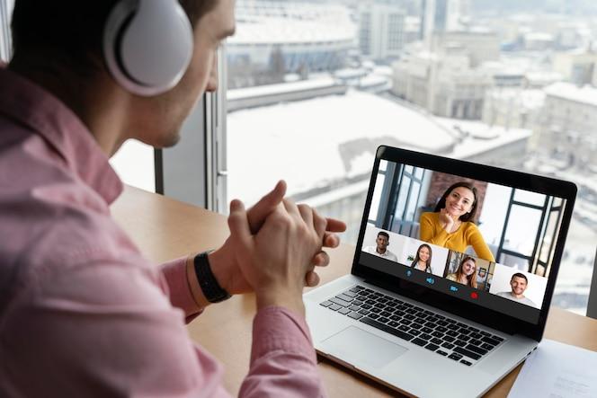 Hombre que tiene una videollamada en línea con compañeros de trabajo