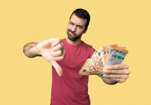 Hombre que toma mucho dinero mostrando el pulgar hacia abajo con ambas manos sobre fondo amarillo aislado