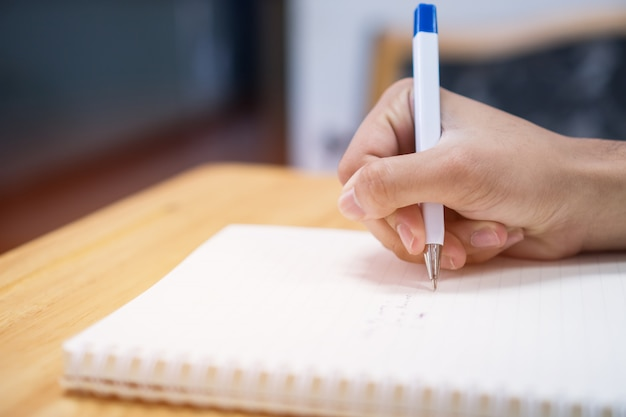 Hombre que toma y que escribe notas en el cuaderno con la pluma en biblioteca en la universidad de la universidad