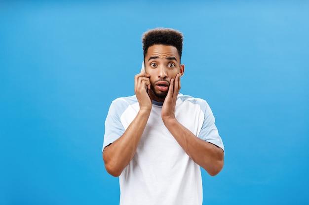 Hombre que toma el teléfono escuchando noticias terribles sintiéndose conmocionado y preocupado sosteniendo el teléfono inteligente cerca de la boca de apertura de la oreja, frunciendo el ceño y tocando la cara por la conmoción preocupándose por la salud de un amigo sobre la pared azul.